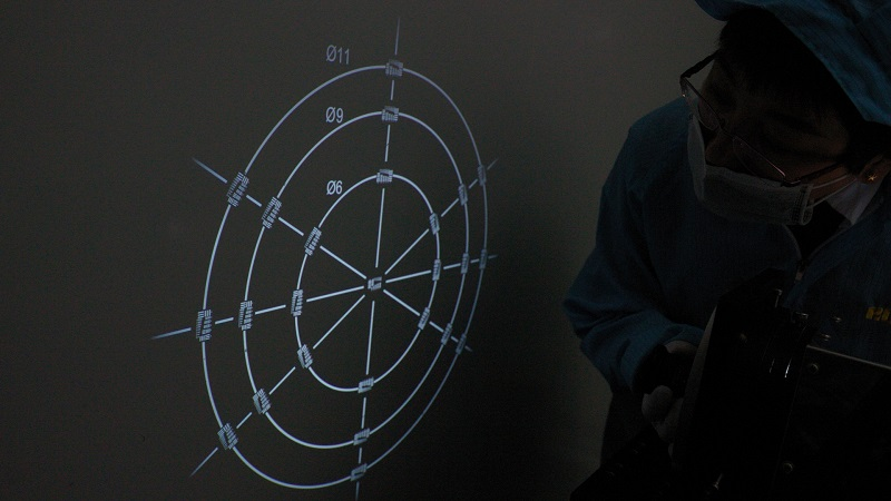 "An operator performing a reverse projection test. The circles labeled 11, 9, and 6 correspond to image circles of 2/3"", 1/1.8"", and 1/3"" sensors, respectively."